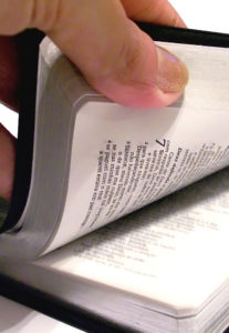 Person turning pages of Bible